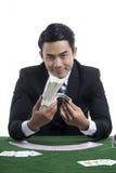 O homem considerável no terno preto que guarda pilhas dos dólares nas mãos Foto de Stock Royalty Free