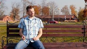 O homem considerável novo com cerdas está sentando-se em um banco no parque em um bom humor e está agarrando-se seus dedos, espaç filme
