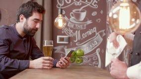 O homem considerável novo em um contador da barra bebe a cerveja e olha seu smartphone filme