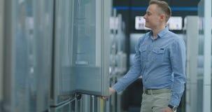 O homem considerável novo escolhe um refrigerador para a compra Abre a porta e inspeciona o dispositivo, examina os preços video estoque