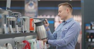O homem considerável novo escolhe uma chaleira elétrica comprar Inspeciona o dispositivo, examina os preços e filme