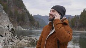 O homem considerável novo está no banco do rio da montanha no tempo frio, indivíduo farpado que fala no telefone Movimento lento vídeos de arquivo