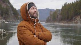 O homem considerável novo está no banco do rio da montanha no tempo frio Movimento lento vídeos de arquivo