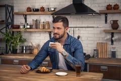 O homem considerável novo está sentando-se em sua cozinha na manhã que come seu café, croissant e um suco e um pensamento de maçã imagem de stock
