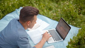O homem considerável novo está trabalhando no portátil que encontra-se no parque no verão vídeos de arquivo