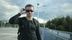 O homem considerável novo no roupa apropriada agradável remove e veste óculos de sol e sorriso Paisagem urbana video estoque