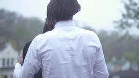 O homem considerável põe seu revestimento sobre os ombros fêmeas indivíduo e a amiga que passa o tempo acopla-se junto no amor vídeos de arquivo