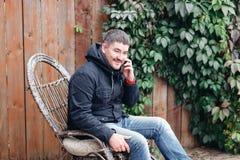 O homem considerável relaxa na balançar-cadeira do vintage com o telefone no jardim imagem de stock royalty free