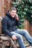 O homem considerável relaxa na balançar-cadeira do vintage com o telefone no jardim fotografia de stock royalty free
