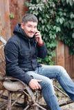 O homem considerável relaxa na balançar-cadeira do vintage com o telefone no jardim imagens de stock royalty free