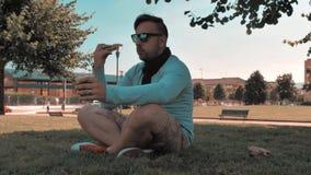 o homem considerável relaxa no parque do distrito da cidade video estoque