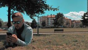 o homem considerável relaxa no parque do distrito da cidade vídeos de arquivo
