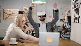O homem considerável tenta o app para vidros da realidade virtual do capacete de VR seus amigos e colegas que apoiam o no escritó imagem de stock