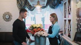 O homem considerável vem a um florista e pergunta a florista sobre flores video estoque