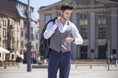 O homem considerável vestiu elegantemente a vista de seu relógio Imagens de Stock