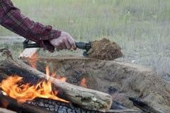 O homem constrói o fogo Pit Around Open Camp Fire Fotos de Stock