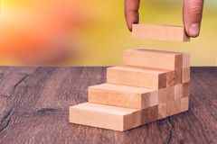 O homem constrói uma escada de madeira Conceito: desenvolvimento estável imagem de stock royalty free