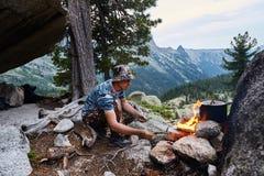 O homem construiu uma fogueira nas madeiras na natureza Sobreviva nas montanhas na floresta, cozinhando em uma bandeja do potenci foto de stock