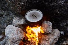 O homem construiu uma fogueira nas madeiras na natureza Sobreviva nas montanhas na floresta, cozinhando em uma bandeja do potenci fotos de stock royalty free