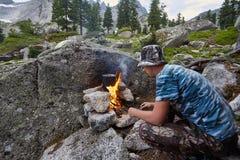 O homem construiu uma fogueira nas madeiras na natureza Sobreviva nas montanhas na floresta, cozinhando em uma bandeja do potenci imagem de stock royalty free