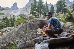 O homem construiu uma fogueira nas madeiras na natureza Sobreviva nas montanhas na floresta, cozinhando em uma bandeja do potenci imagem de stock