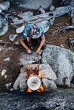 O homem construiu uma fogueira nas madeiras na natureza Sobreviva nas montanhas na floresta, cozinhando em uma bandeja do potenci imagens de stock royalty free