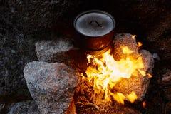 O homem construiu uma fogueira nas madeiras na natureza Sobreviva nas montanhas na floresta, cozinhando em uma bandeja do potenci fotos de stock