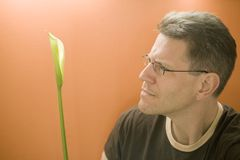 O homem contempla um lírio de Calla imagens de stock