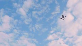 O homem controla o zangão, o zangão está voando altamente no céu, a câmera segue o zangão video estoque