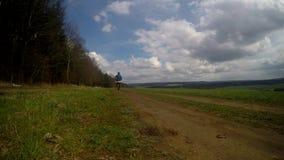 O homem corre em uma estrada de floresta na vila filme