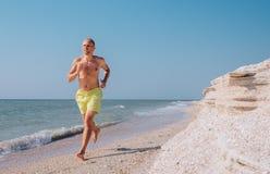 O homem corre na linha da ressaca do mar com os pés descalços Fotos de Stock Royalty Free
