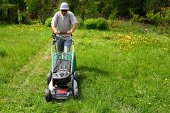 O homem corta o gramado com uma segadeira da combustão no jardim do quintal fotografia de stock