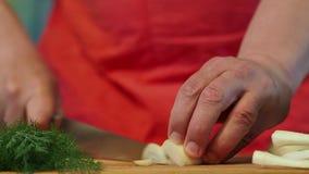 O homem corta meios anéis das cebolas filme