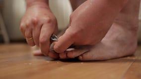 O homem corta ordenadamente seu close-up das unhas do p? Um homem faz-se um pedicure em casa no assoalho filme