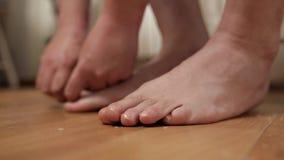 O homem corta ordenadamente seu close-up das unhas do p? Um homem faz-se um pedicure em casa no assoalho video estoque