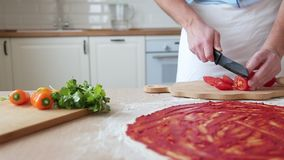 O homem corta os tomates para a pizza video estoque