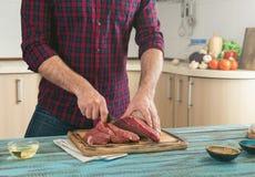 O homem corta a parte de carne na placa de corte de madeira Fotos de Stock Royalty Free