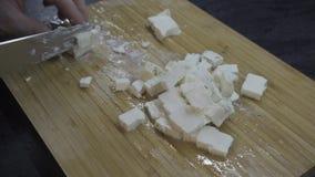 O homem corta o queijo em uma placa de madeira filme