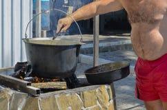 O homem cozinha o alimento na natureza em um potenciômetro em um fogo aberto fotos de stock