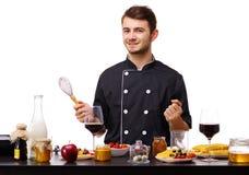 O homem, cozinheiro, está estando na cozinha, pronta para começar o trabalho fotos de stock royalty free
