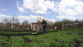 O homem cultiva a terra no jardim com um rebento, preparando o solo para semear filme