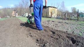 O homem cultiva a terra no jardim com um rebento, preparando o solo para semear video estoque