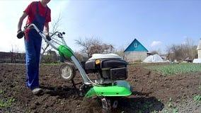 O homem cultiva a terra no jardim com um rebento, preparando o solo para semear vídeos de arquivo