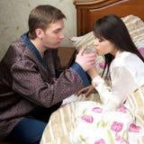 O homem dá a água fresca à mulher doente fotografia de stock