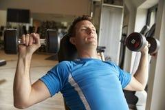 O homem dá certo com pesos em um banco em um gym, vista dianteira Imagens de Stock Royalty Free