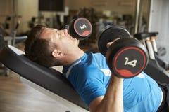 O homem dá certo com pesos em um banco em um gym, vista lateral Imagem de Stock
