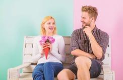 O homem dá flores do ramalhete à amiga, fundo de turquesa Pares na data romântica do amor O cavalheiro traz sempre fotos de stock