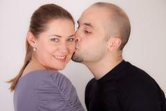 O homem dá a mulher um beijo Foto de Stock