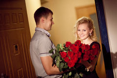 O homem dá rosas a uma menina imagens de stock