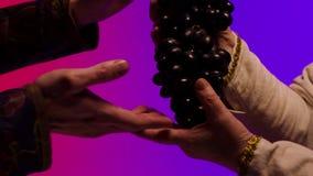 O homem dá um grupo de uvas grandes, pretas, suculentas às mãos da mulher adulta, isoladas no fundo colorido estoque Feche acima  filme